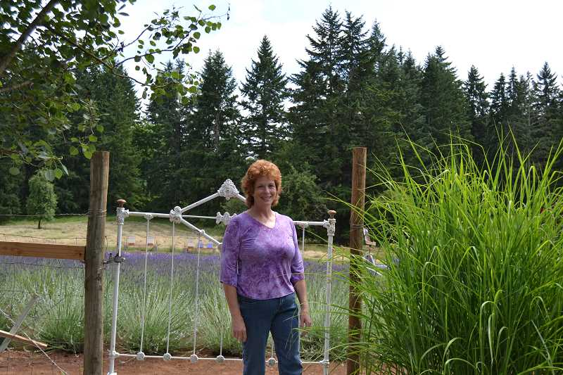 by: CINDY FAMA - Janna Liewergen stands by the gate to The Meadow of Lavender 30939 S Oswalt Road. It will be part of the Oregon Lavender Festival tour July 12-13.
