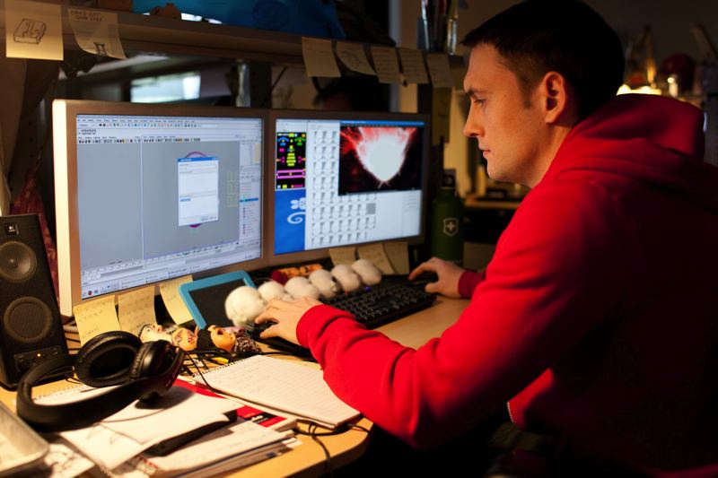 by: COURTESY OF LAIKA INC./FOCUS FEATUES - Adam Lawthers works on computer graphics during production of 'ParaNorman.'