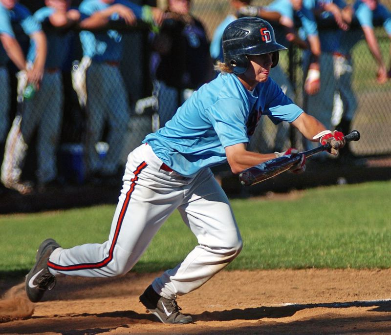by: DAN BROOD - FUNDAMENTALS -- Suburban Door's Chase Anderson puts down a bunt during the first game of the Dawgs' doubleheader sweep of Forest Grove.