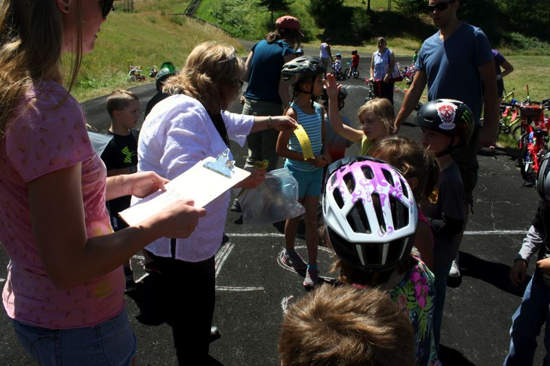 by: POST PHOTO: KYLIE WRAY - First Princess Barb Clare helps pass out ribbons to 6-year-old racers.