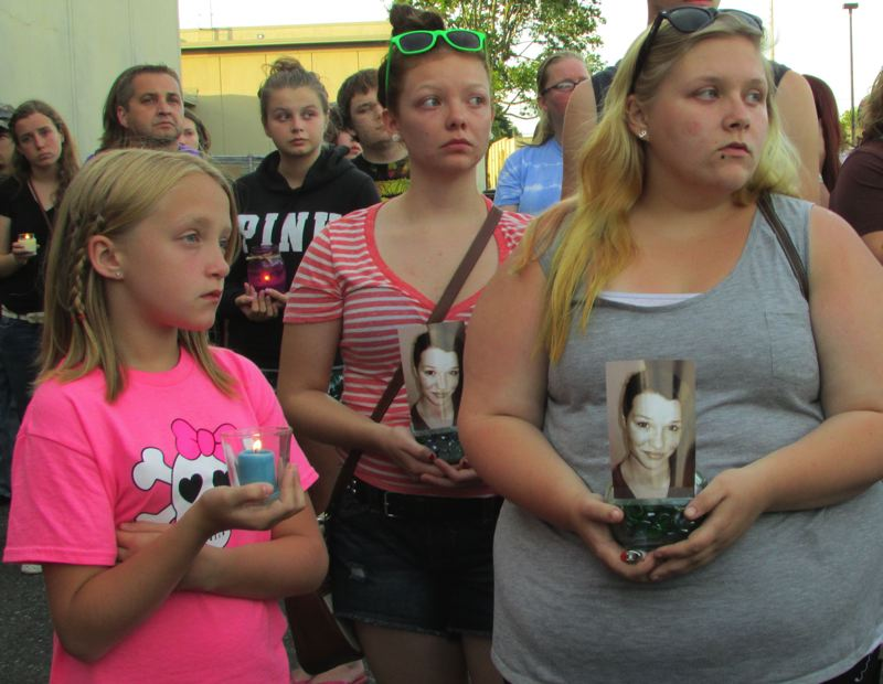 by: COURTNEY VAUGHN - Kierra Skinner, Alyssa Richardson and Kelsey Reid gather with candles at St. Helens High School to remember Seeaira Hicks. More than 150 people showed up to a candlelight vigil held Tuesday evening for the late teen.