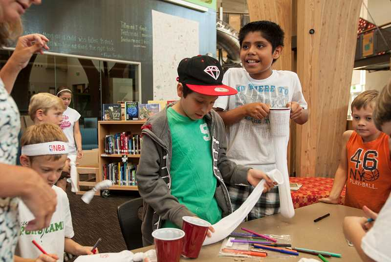 by: SPOKESMAN PHOTO: JOSH KULLA - Zaid Bautista, 11, takes part in a craft session with his friend, Tony Calderon, as part of Lowrie Primary School's summer library program. Both boys will be fifth-graders at Lowrie in the fall.
