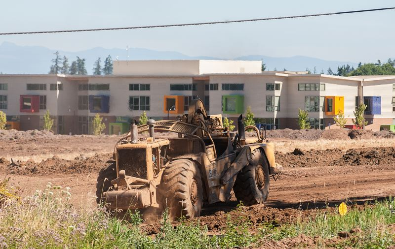 by: SPOKESMAN PHOTO: JOSH KULLA - Work is already underway on demolition of SW 110th Avenue. Shown here, an earth mover heads south on what eventually will become Villebois Drive. Lowrie Primary School is in the background.