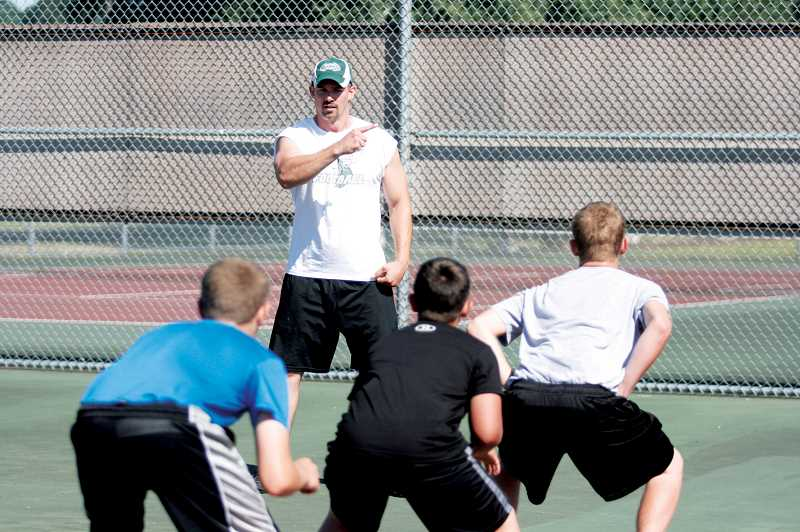 by: PHIL HAWKINS - North Marion tennis coach Caleb Barnes instructs students during the Husky Boot Camp.