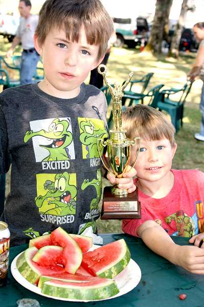 by: PEGGY SAVAGE - Last year's watermelon eating champion shows off his trophy to his little brother. The kids watermelon eating contest starts at 3 p.m.. Saturday.