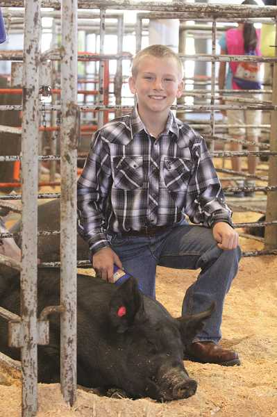 by: LINDSAY KEEFER - Brody Schindler, a fourth-grader from St. Paul, poses with his pig at the Marion County Fair right after winning first place in showmanship the first day of the fair. He went on to be named reserve champion in the novice division.