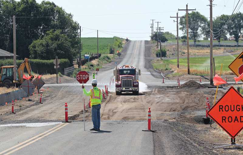 by: HOLLY M. GILL - Flaggers control traffic at the intersection of Dover Lane and U.S. Highway 26, where ODOT is making safety improvements.
