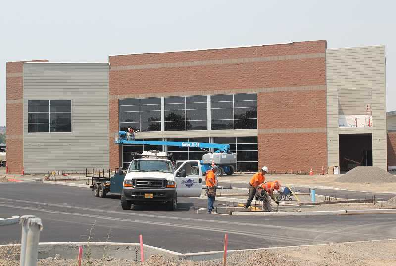 by: HOLLY M. GILL - A construction crew works on walkways and curbs in front of the new Performing Arts Center on Wednesday.