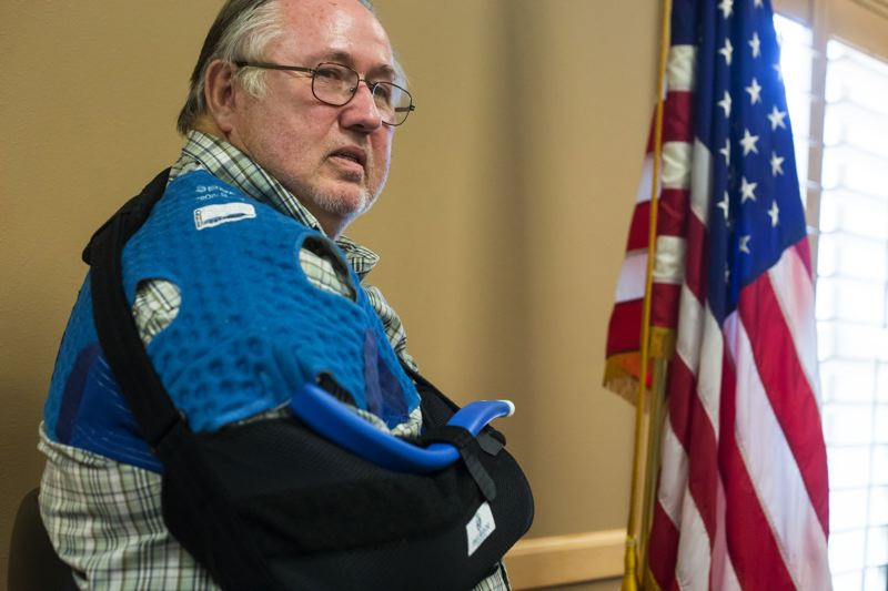 by: TIMES PHOTO: JONATHAN HOUSE - Beaverton resident and military veteran Robert Gustafson stands by the U.S. flag in the Veterans of Foreign Wars Post 3452 building in Tualatin. Gustafson is the second Save Our Veterans patient to have complimentary surgery since the program kicked off in early July.