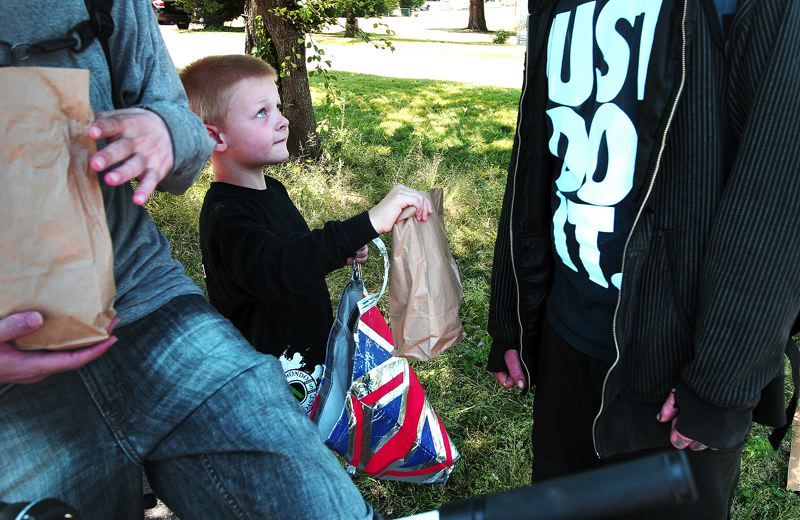 by: OUTLOOK PHOTO: JIM CLARK - Jackson Clark offers a sack lunch to a man behind the Gresham Post Office. The 6-year-old started a mission to feed the hungry more than a year ago, after his mom explained what it meant to be homeless.