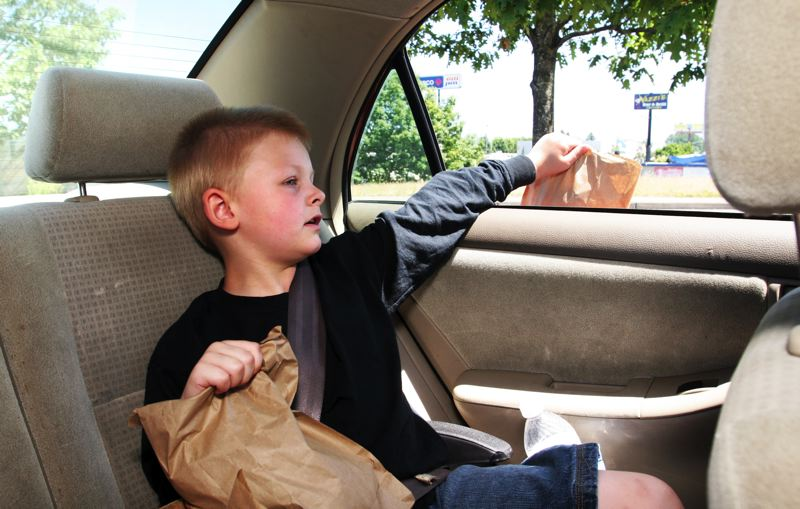 by: OUTLOOK PHOTO: JIM CLARK - The family travels with a box in the back seat to carry Jacksons lunches. When they come across someone standing on a street median, Jackson rolls down his window and hands them a brown bag lunch.