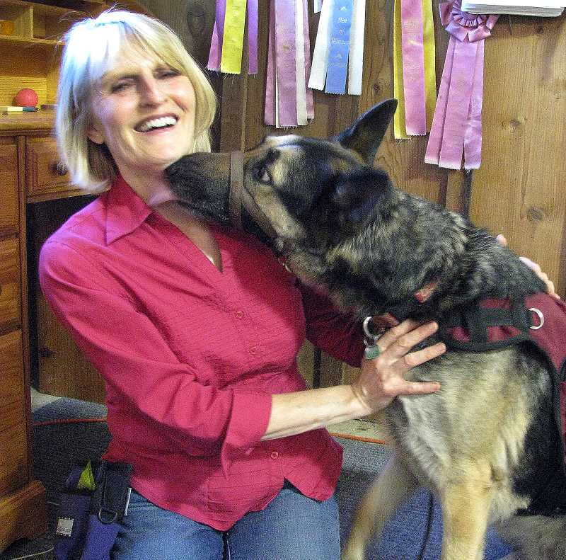 by: OUTLOOK PHOTO: LAURA KNUDSON  - Cheryl Mulick, a volunteer for Paws Assisting Veterans, receives a kiss from one of the service dogs she is training.