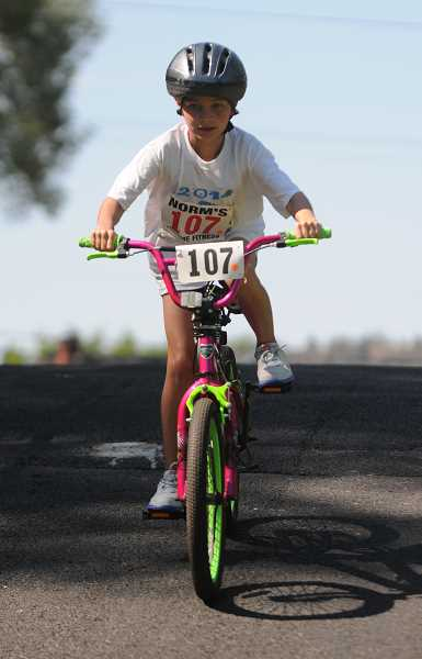 by: LON AUSTIN/CENTRAL OREGONIAN - Ava Brenneman rides her bike down a hill at the start of the bicycle portion of the 1/2 Fast Triathlon last Saturday. Brenneman finished third in the  7 to 8 year-old division of the event. A total of 28 5-12 year-olds participated in the event.