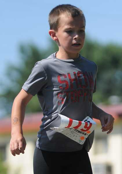 by: LON AUSTIN/CENTRAL OREGONIAN - Brady Housley races to the finish line to win the 7 to 8 year-old age group of the 1/2 Fast Triathlon.