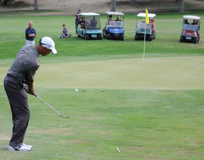 by: LON AUSTIN/CENTRAL OREGONIAN - Vince Johnson plays a chip shot onto the seventh green at Prineville Golf Club during Friday's horse race. Johnson, who finished fourth in the event, went on to win the Prineville Invitational Pro-Am with a four under par 128.
