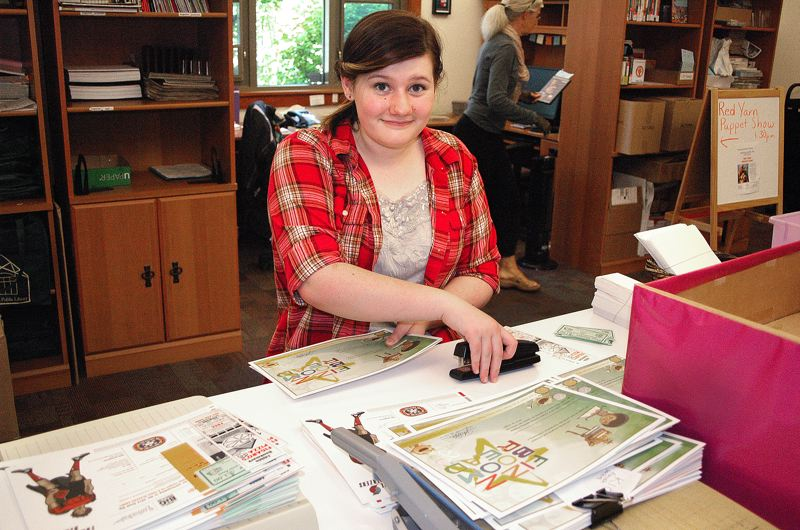 by: OUTLOOK PHOTO: BEVERLY CORBELL - Estacada Library volunteer, Megan Flor, who will be a freshman at Estacada High this fall, puts together information packets for the Summer Reading Program to be distributed at the Estacada Summer Festival.