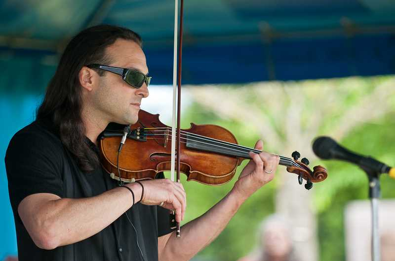 by: SPOKESMAN FILE PHOTO: JOSH KULLA - Concert rock violinist Aaron Meyer, shown here at Wilsonvilles Festival of Art, is staying as busy as ever alongside renowned guitarist and producer Tim Ellis. The pair and their 6-piece band play at Town Center Park on July 31.