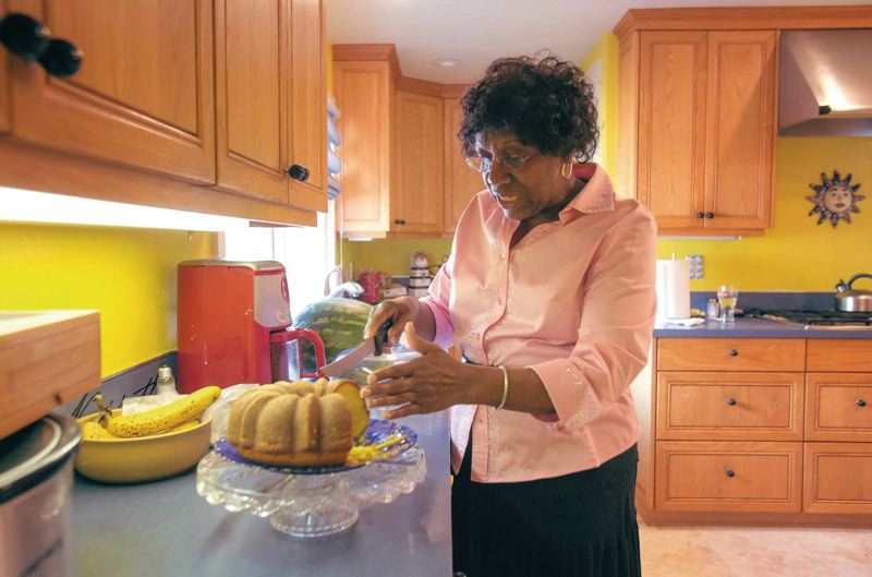 by: TRIBUNE PHOTO: JONATHAN HOUSE - Margaret Carter slices a lemon pound cake in her home as she welcomed guest. Carter firmly believes that, When you share your bread, people will come to common ground.