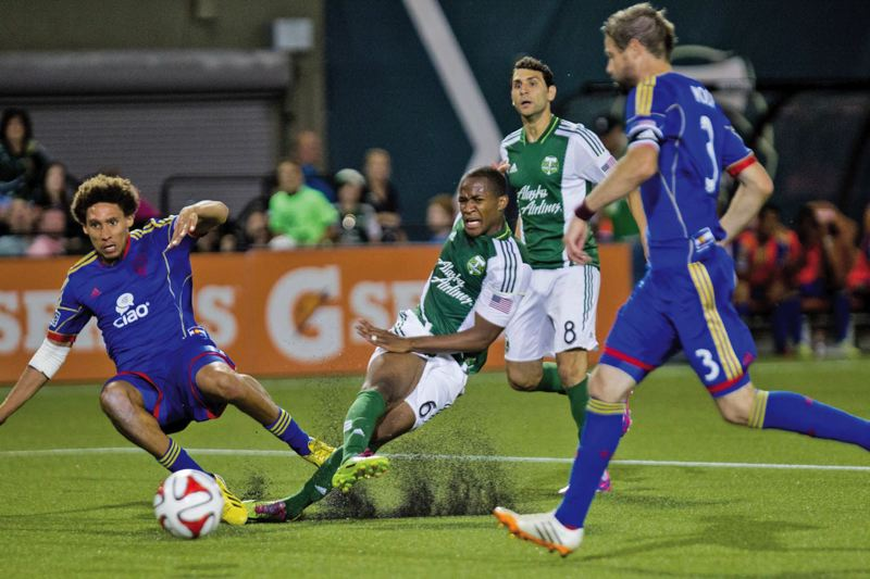 by: COURTESY OF DAVID BLAIR - Darlington Nagbe of the Portland Timbers digs up some turf as he fights for the ball against the Colorado Rapids. Portland won last weeks MLS game, 2-1.