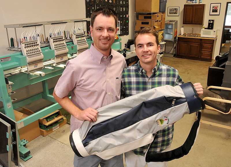 by: REVIEW, TIDINGS PHOTO: VERN UYETAKE - Matt Lemman, left, and his brother Tim hold the new version of the Jones Golf Bag. The Lake Oswego family wants the item to regain its status as the golf bag of choice for golfers in the Portland area.