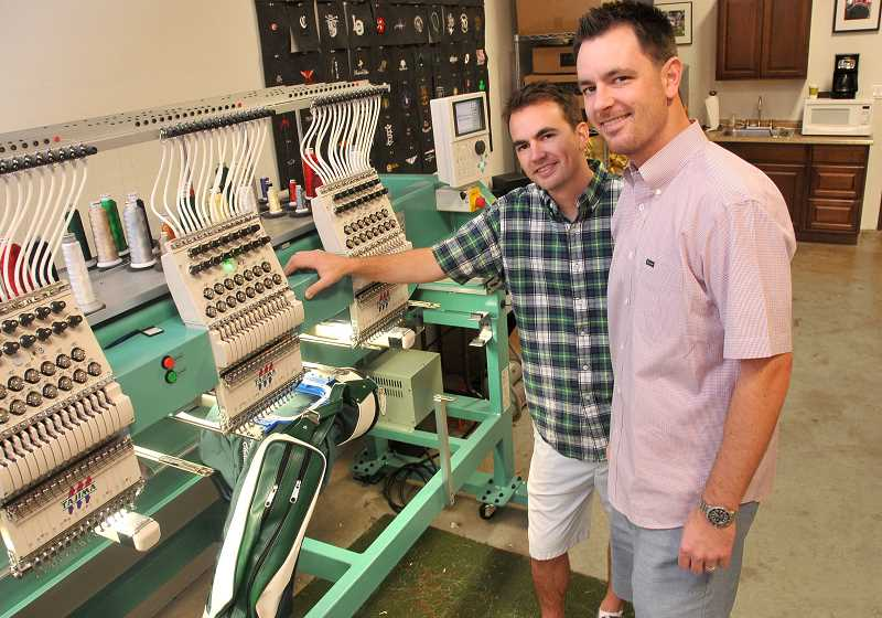 by: REVIEW, TIDINGS PHOTO: VERN UYETAKE - Tim, left, and Matt Lemman show the high tech embroidering machiner used to label the famous Jones Golf Bag at their shop at Bridgeport Village.