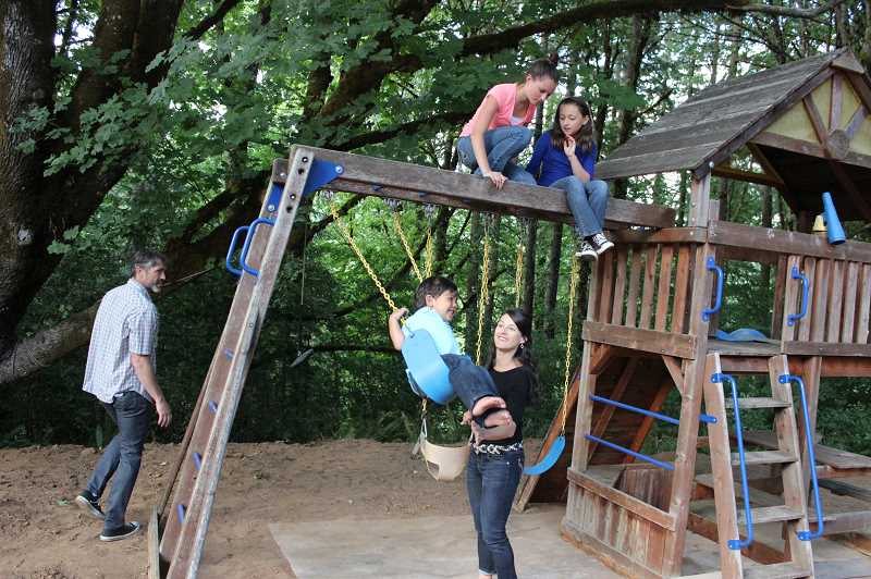 Photo Credit: KATE STRINGER - Brandi Frye and her family play on their swing set in the backyard of their Forest Grove home. Frye makes time to play hard with her family, hiking, camping or visiting the Oregon Coast together.