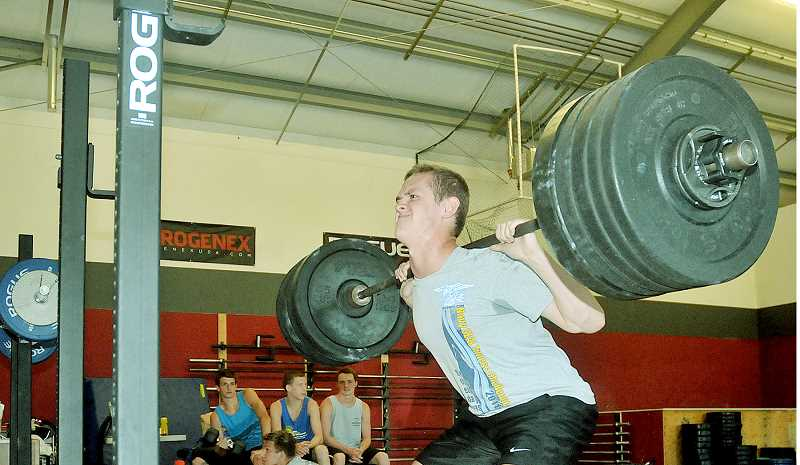by: SETH GORDON - Beast mode - Senior goalie Kyle Hansen squats 245 pounds Monday during the Chehalem water polo team's dry-land workout at Newberg Crossfit.