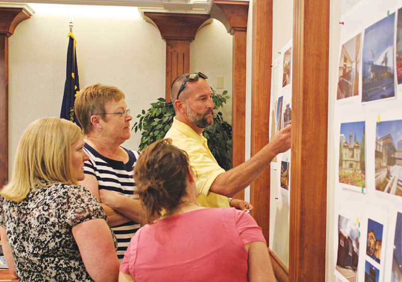 by: HOLLY M. GILL - From left, County Counsel Alexa Gassner, county administrative assistant Barb Andresen, Courtney Quale, and Kurt Symons, community corrections director, check out photos of other courthouses around the state and mark the courthouse projects they find most appealing and unappealing.