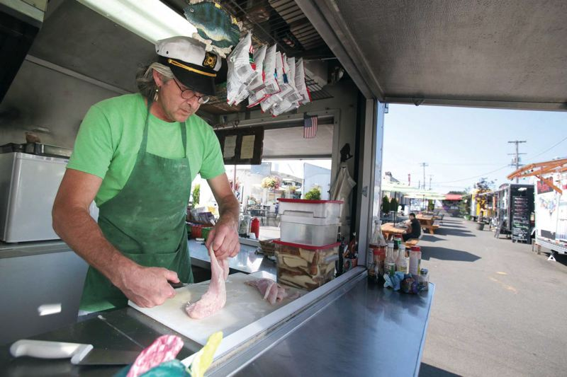 by: TRIBUNE PHOTO: JONATHAN HOUSE - Ed MacGregor, who operates Year of the Fish at a la carts Food Pavilion, worries the site could get redeveloped, displacing the popular food cart pod.