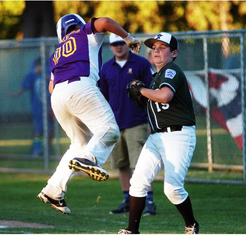 by: DAN BROOD - NO ESCAPE -- Hermiston's Miguel Moreno (left) tries to leap away, but he is tagged out by Tigard first baseman Sean Murphy during the fifth inning of last week's state championship game.
