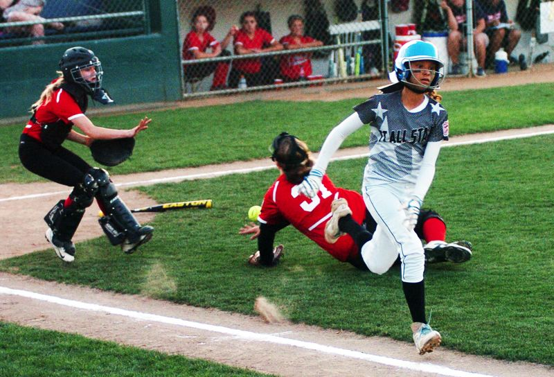by: DAN BROOD - Kendra Zuckerman (right) sprints to first base after putting down a bunt single in the fourth inning of the District 4 championship game.