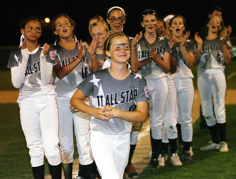 by: DAN BROOD - Tigard/Tualatin City shortstop Bella Valdes goes up to receive her district championship medal.