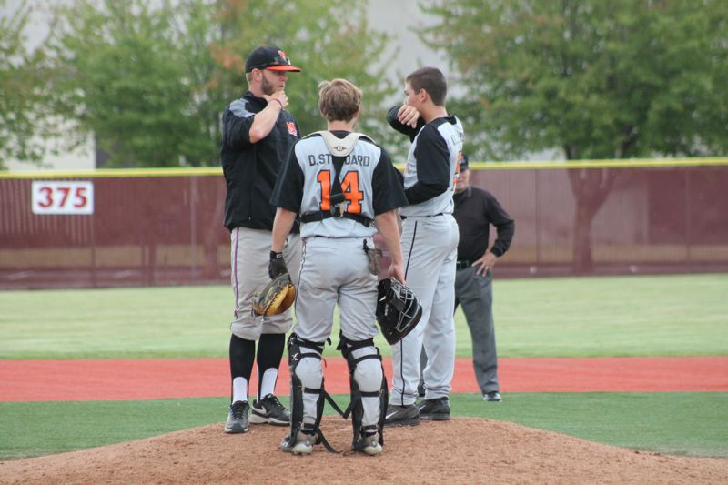 by: JIM BESEDA/MOLALLA PIONEER - Molalla assistant coach Mitch Huff (left) chats with catcher Daniel Stoddard and relief pitcher Aaron Alexander during the fifth inning of Thursday's 11-9 loss to Dallas at Western Oregon University in Monmouth.