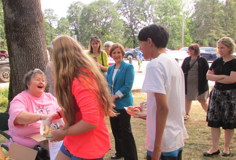 by: MARK MILLER - Barb Weaver (left) greets teenagers at McCormick Park, where she hands out snacks and peanut butter and jelly sandwiches as part of the St. Helens School District's summer food service program, as U.S. Rep. Suzanne Bonamici (center) looks on.