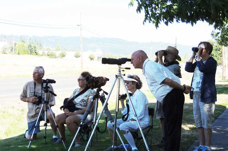 by: HILLSBORO TRIBUNE PHOTO: DEBBY DE CARLO - Dennis Manzer (center) has drawn hundreds of curious onlookers to the spot near 185th Avenue and West Union Road, where he set up a few spotting scopes to wait for an eaglets first flight.