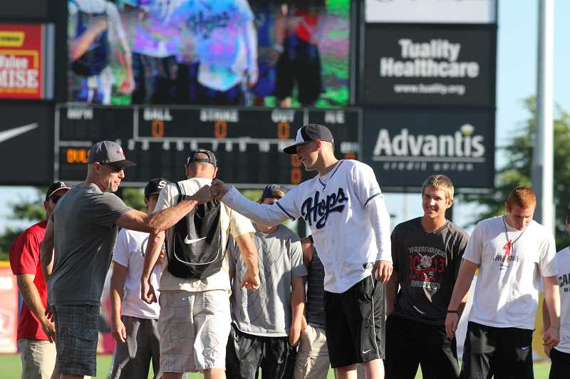 Photo Credit: HILLSBORO TRIBUNE PHOTO: AMANDA MILES - Aaron Ahlstron (in Hops jersey) is greeted by Clackamas teammates and coaches on the field before he throws out the first pitch at last Thursdays Hillsboro Hops game. Ahlstrom, 18, a recent Clackamas High School graduate, is battling brain cancer.