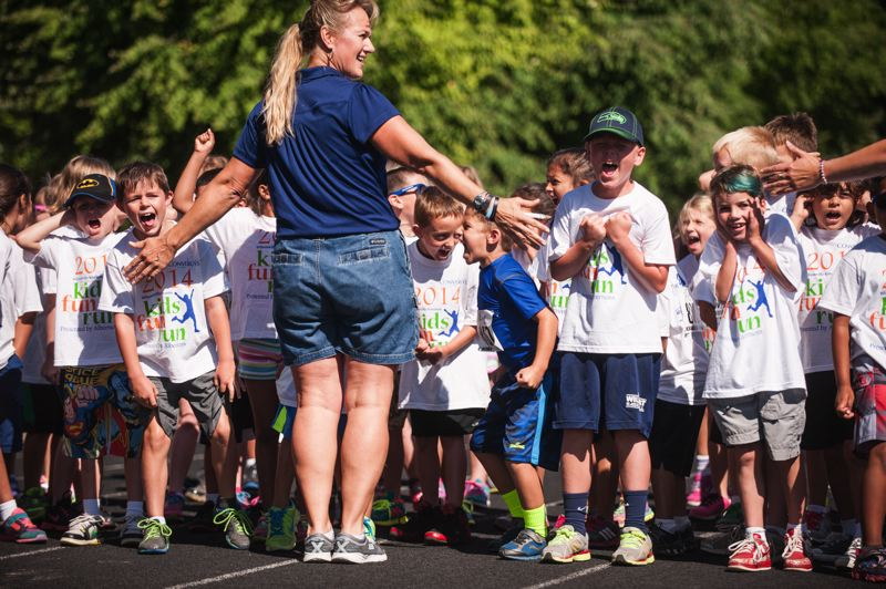 by: SPOKESMAN PHOTO: JOSH KULLA - Local chiropractor Laura LaJoie (blue shirt) directs traffic at the start of a heat Saturday at the Kiwanis Kids Fun run.