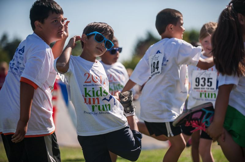 by: SPOKESMAN PHOTO: JOSH KULLA - Kids learned to stretch before exercising at the Kiwanis Kids Fun Run.