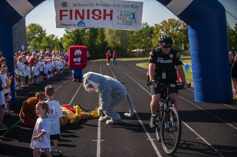 by: SPOKESMAN PHOTO: JOSH KULLA - Wilsonville Police Sgt. Dan Kraus 'wins' the mascot race Saturday at the Wilsonville Kids Fun Run.