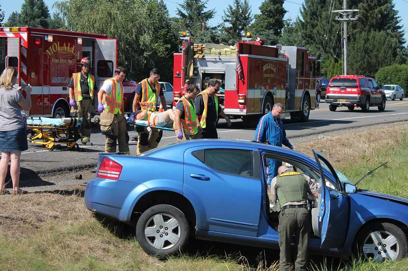 by: JIM BESEDA/MOLALLA PIONEER - Emergency personnel with Molalla Rural Fire District No. 73 carried an injured driver by stretcher to an awaiting LifeFlight helicopter Monday afternoon following a head-on collision on Highway 213 near South Macksburg Road.