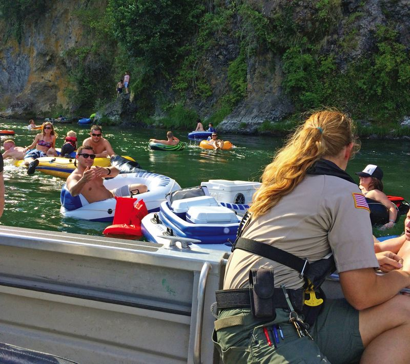 Photo Credit: TRIBUNE PHOTO SHASTA KEARNS MOORE - Clackamas County Marine Services Officer Abigail Hunt helps ensure floater safety on the popular Clackamas River float from Barton to Carver Parks. Two people have drowned near this location in the past five years.