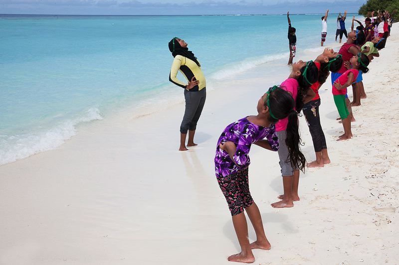 by: CONTRIBUTED PHOTO: CAT VINTON PHOTOGRAPHY - Students stretch on the shore of Kunfunadhoo Island, where the Maldivian resort Soneva Fushi is located, before swim lessons.