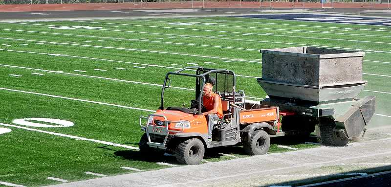 by: SETH GORDON - Ready for football - Field Turf employee Jake Robert fills the artificial turf at the Stoffer Family Stadium July 17. With the field completed, constructing the uncovered grandstands and installing the video scoreboard are the final projects remaining to be completed before the George Fox football team hosts Arizona Christian Sept. 6.