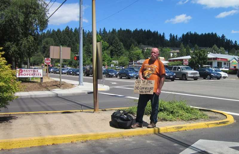 by: BARBARA SHERMAN - HAND OUT OR HAND UP? - This man, standing on an island in Royalty Parkway just inside the King City city limits next to 99W, is a frequent visitor to the spot, and some local residents want city officials to 'do something' to eliminate panhandling.
