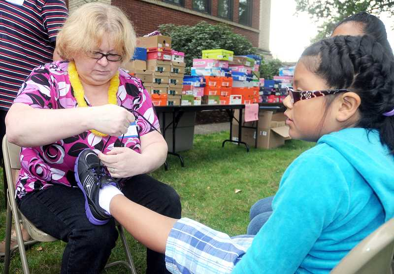 by: GARY ALLEN - Happy feet - Last year the Newberg Roots Church gave away hundreds of pairs of new shoes just prior to the beginning of school.