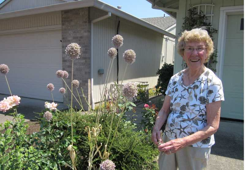 by: BARBARA SHERMAN - THERE ARE A FEW 'FARM' TOUCHES AROUND HER YARD - Maxine and Carl Leach moved to Summerfield in 1989, so Maxine, standing beside elephant garlic along the driveway, has now lived there for 25 years, and all her children live in the metro area.