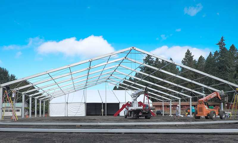 by: RAY HUGHEY - The temporary livestock barn at the Clackamas County Event Center fairgrounds goes up quickly.