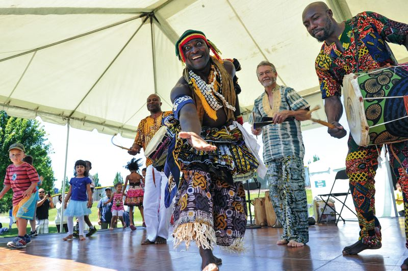 by: TIMES PHOTOS: JOHN LARIVIERE - Mathias Galley dances to traditional Ghanaian drum rhythms as the Mathias Galley African Dance Ensemble perform as part of the Beaverton International Celebration during Saturday's Party in the Park. Other members of the troupe are Mashud Neindo (back left), Jeff Strang (back center) and Boinor Nartey Jr. (back right).