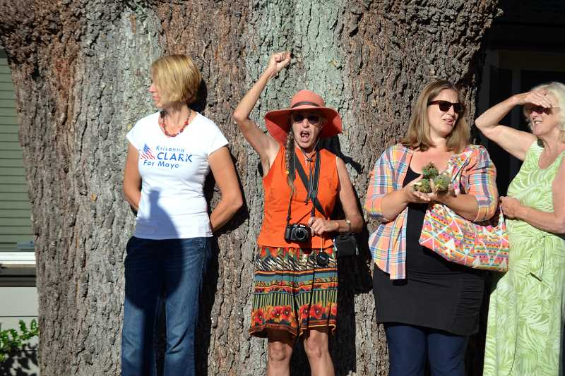 Photo Credit: GEOFF PURSINGER - June Reynolds chants 'Save Our Tree' with a group of protestors next to the Cedar of Lebanon tree in Sherwood. The tree was cut down Tuesday because it posed a safety risk to residents, property owners said.
