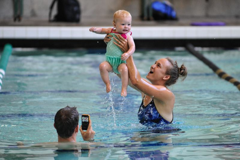 by: TIMES PHOTOS: JOHN LARIVIERE - Michael and Ricole Brown of Southwest Portland record the memory of participating in the swimming portion of the Family Triathlon with their 1-year-old daughter Oaklyn at the Tualatin Hills Aquatic Center.